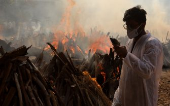 A relative stands next to the burning funeral pyres of those who died due to the coronavirus disease (COVID-19), at Ghazipur cremation ground in New Delhi. In India the highest single-day spike in coronavirus infection. The report recorded 352,991 new Covid-19 cases and 2,812 deaths in the last 24 hours amid an oxygen crisis. - Naveen Sharma / SOPA Images//SOPAIMAGES_08380021/2104270904/Credit:SOPA Images/SIPA/2104270907