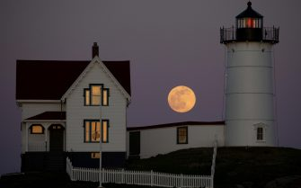 epaselect epa09162763 The Super Pink Moon is seen rising behind the Nubble Lighthouse on Cape Neddick, in York, Maine, USA, 26 April 2021. The super full moon is named this way because it is at its closest to earth and thus appears bigger than a normal full moon. Cape Neddick Light Station was dedicated by the US Lighthouse Service and put into use in 1879 and is still in use today.  EPA/CJ GUNTHER