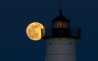 epa09162767 The Super Pink Moon is seen rising behind the Nubble Lighthouse on Cape Neddick, in York, Maine, USA, 26 April 2021. The super full moon is named this way because it is at its closest to earth and thus appears bigger than a normal full moon. Cape Neddick Light Station was dedicated by the US Lighthouse Service and put into use in 1879 and is still in use today.  EPA/CJ GUNTHER