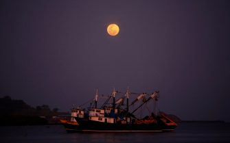 epa09162737 Two boats sail near the coast under the pink Supermoon that rises in the sky, in the fishing town of Puerto Caimito, Panama, 26 April 2021.  EPA/Bienvenido Velasco