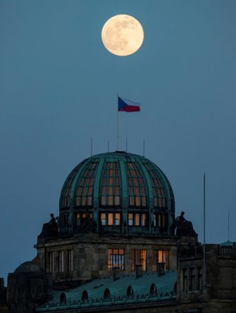 epa09162416 The so-called Super Pink Moon rises over Prague, Czech Republic, 26 April 2021. The super full moon is named this way because it is at its closest to earth and thus appears bigger than a normal full moon.  EPA/MARTIN DIVISEK