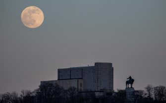 epa09162415 The so-called Super Pink Moon rises behind the Vitkov Memorial in Prague, Czech Republic, 26 April 2021. The super full moon is named this way because it is at its closest to earth and thus appears bigger than a normal full moon.  EPA/MARTIN DIVISEK