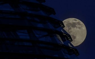 epa09162516 Super full moon rises behind German Parliament  Bundestag  in Berlin, Germany, 26 April 2021. The super full moon is named this way because it is at its closest to earth and thus appears bigger than a normal full moon.  EPA/FILIP SINGER