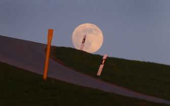 """26 April 2021, Bavaria, Bernbeuren: The full moon rises behind a country road leading over a hilltop. On 27 April 2021 there is a so-called """"supermoon"""". Then the distance between the moon and the earth is smaller than usual. Photo: Karl-Josef Hildenbrand/dpa"""