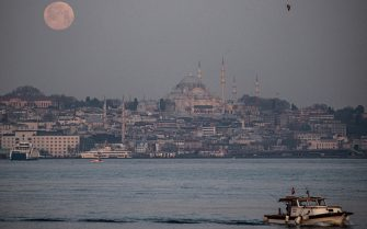 epa09162784 A fisherman labors at the Bosphorus in view of the waning super full moon, next to the Suleymaniye Mosque (C) during sunrise, in Istanbul, Turkey, 27 April 2021. The super full moon is named this way because it is at its closest to earth and thus appears bigger than a normal full moon.  EPA/SEDAT SUNA
