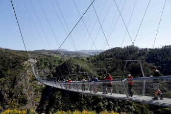 epa09164743 People walk across '516 Arouca', considered the largest pedestrian suspension bridge in the world, at 516 meters long and 175 meters high, in Arouca, Portugal, 16 April 2021 (issued 28 April 2021). The bridge is secured by steel cables arranged 175 meters above the Paiva riverbed and can be visited by the general public from 03 May.  EPA/ESTELA SILVA