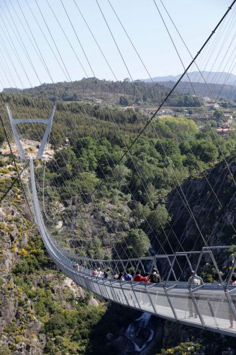 epa09164742 People walk on '516 Arouca', considered the largest pedestrian suspension bridge in the world, at 516 meters long and 175 meters high, in Arouca, Portugal, 16 April 2021 (issued 28 April 2021). The bridge is secured by steel cables arranged 175 meters above the Paiva riverbed and can be visited by the general public from 03 May.  EPA/ESTELA SILVA