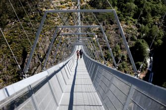 epa09164741 Two people walk on '516 Arouca', considered the largest pedestrian suspension bridge in the world, at 516 meters long and 175 meters high, in Arouca, Portugal, 16 April 2021 (issued 28 April 2021). The bridge is secured by steel cables arranged 175 meters above the Paiva riverbed and can be visited by the general public from 03 May.  EPA/ESTELA SILVA