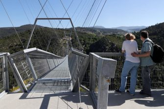 epa09164739 Two people view '516 Arouca', considered the largest pedestrian suspension bridge in the world, at 516 meters long and 175 meters high, in Arouca, Portugal, 16 April 2021 (issued 28 April 2021). The bridge is secured by steel cables arranged 175 meters above the Paiva riverbed and can be visited by the general public from 03 May.  EPA/ESTELA SILVA