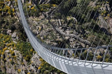epaselect epa09164744 A view of '516 Arouca', considered the largest pedestrian suspension bridge in the world, at 516 meters long and 175 meters high, in Arouca, Portugal, 16 April 2021 (issued 28 April 2021). The bridge is secured by steel cables arranged 175 meters above the Paiva riverbed and can be visited by the general public from 03 May.  EPA/ESTELA SILVA