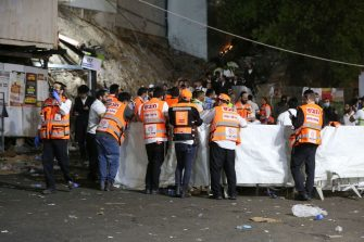 Emergency workers gather at the scene after dozens of people were killed and others injured after a grandstand collapsed in Meron, Israel, where tens of thousands of people were gathered to celebrate the festival of Lag Ba'omer at the site in northern Israel early on April 30, 2021. - Dozens of people were killed in a stampede at a Jewish pilgrimage site in the north of Israel on early on April 30, rescue services said.  Tens of thousands of Jews were participating in the annual pilgrimage on Thursday, for the feast of Lag BaOmer. But after midnight, a grandstand collapsed, triggering scenes of panic. - Israel OUT (Photo by David COHEN / JINI PIX / AFP) / Israel OUT (Photo by DAVID COHEN/JINI PIX/AFP via Getty Images)