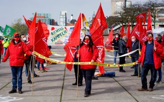 01 May 2021, Hamburg: Participants of the main rally of the German Trade Union Confederation (DGB) on Labour Day wave flags of the GEW trade union at the Hamburg fish market. Photo: Axel Heimken/dpa