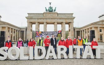 """01 May 2021, Berlin: """"Solidarity"""" is written in large letters in front of the Brandenburg Gate. Members of different trade unions stand behind it during the DGB rally with delegations of the Berlin trade unions. Photo: Annette Riedl/dpa"""