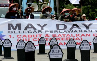 epa09170880 Activists hold a banner while standing in front of mock tombstones reading 'rest in peace, work creation law' during a rally to mark International Workers' Day, or May Day, in Jakarta, Indonesia, 01 May 2021.  EPA/Bagus Indahono