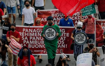 epa09170750 Demonstrators carry placards during a protest to mark Labor Day in Quezon City, Metro Manila, Philippines, 01 May 2021. Various cause-oriented groups pushing for labor rights protested in Manila with calls for an increase in financial assistance due to COVID-19 and mass testing among others.  EPA/MARK R. CRISTINO