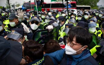 epa09170991 Members of South Korean Confederation of Trade Unions (KCTU) scuffle with police officials (L) as they try to march in a rally marking Labor Day in Seoul, South Korea, 01 May 2021. The protesters gathered to rally for labor reform and better working conditions.  EPA/JEON HEON-KYUN
