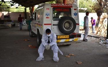 epa09167847 A worker in personal Protective Equipment (PPE) rests near an ambulance at a cremation ground  in New Delhi, India, 29 April 2021. Delhi reported 25,986 fresh cases, 368 deaths in last 24 hours and continue to struggle with the oxygen supply.  EPA/IDREES MOHAMMED