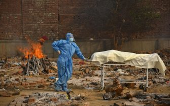 epaselect epa09167849 A Family member, wearing a Personal Protective Equipment (PPE), waits to perform the last rites for COVID-19 victims at a cremation ground in New Delhi, India 29 April 2021. Delhi reported 25,986 fresh cases, 368 deaths in last 24 hours and continue to struggle with the oxygen supply.  EPA/IDREES MOHAMMED