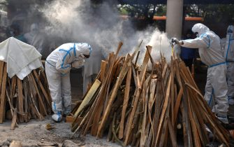 epa09168012 Family member, wearing Personal Protective Equipment (PPE), perform the last rites for COVID-19 victims  at a cremation ground in New Delhi, India, 29 April 2021. Delhi reported 25,986 fresh cases, 368 deaths in last 24 hours and continue to struggle with the oxygen supply.  EPA/IDREES MOHAMMED