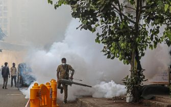 epa09169530 A municipal worker wearing a face mask uses a fumigation spray machine near a vaccination centre in Mumbai, India, 30 April 2021. India has recently recorded a massive surge of fresh COVID-19 cases and deaths, the world's highest single-day rise since the beginning of the pandemic.  EPA/DIVYAKANT SOLANKI