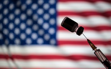 POLAND - 2021/01/24: In this photo illustration a vial of COVID-19 vaccine and a medical syringe displayed over an American flag. (Photo Illustration by Vito Corleone/SOPA Images/LightRocket via Getty Images)