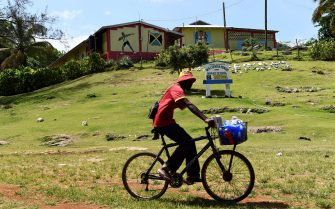 TOPSHOT - A vendor rides past the Waldensia elementary school, where Jamaican sprinter Usain Bolt went for schooling as a kid, in Sherwood Content on June 7, 2017.  Usain Bolt, the greatest sprinter in history with eight Olympic golds, 11 world titles and three world records, will retire from international competition after the IAAF world championships in August. / AFP PHOTO / Jewel SAMAD        (Photo credit should read JEWEL SAMAD/AFP via Getty Images)