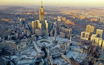 An aerial view shows the Great Mosque and the Mecca Tower in a deserted surrounding on the first day of the Muslim fasting month of Ramdan, in the Saudi holy city of Mecca, on April 24, 2020, during the novel coronavirus pandemic crisis. (Photo by BANDAR ALDANDANI / AFP)
