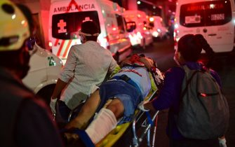 Emergency workers carry an injured person away on a stretcher after an overpass for a metro partially collapsed in Mexico City on May 3, 2021. - At least 13 people were killed and dozens injured in a metro train accident in the Mexican capital on May 3, the authorities said. (Photo by Pedro PARDO / AFP) (Photo by PEDRO PARDO/AFP via Getty Images)