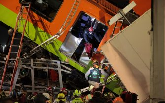 MEXICO CITY, MEXICO - MAY 03: Emergency personnel search for accident survivors after a raised subway track collapsed on May 03, 2021 in Mexico City, Mexico. The Line 12 accident happened between Olivos and Tezonco Metro stations. (Photo by Hector Vivas/Getty Images)