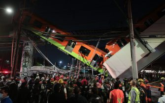MEXICO CITY, MEXICO - MAY 03: Emergency personnel work to search for accident survivors after a raised subway track collapsed on May 03, 2021 in Mexico City, Mexico. The Line 12 accident happened between Olivos and Tezonco Metro stations. (Photo by Hector Vivas/Getty Images)