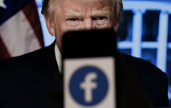 In this photo illustration, a phone screen displays a Facebook logo with the official portrait of former US President Donald Trump on the background, on May 4, 2021, in Arlington, Virginia. - Facebook's independent oversight board was set for a momentous decision on the platform's ban of former US president Donald Trump, as debate swirls on the role of social media in curbing hateful and abusive speech while controlling political discourse. (Photo by Olivier DOULIERY / AFP)