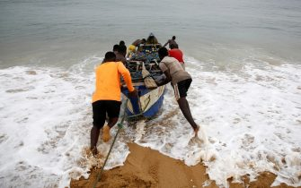 epa09081772 Ivorian artisanal fishermen head out to the sea, outside Abidjan, Ivory Coast, 18 March 2021. Artisanal fishing is the main supplier of fish to Ivorian populations, yet heavy industrial and large scale fishing practices by international companies has increased pressure on traditional fishing communities. Highlighted as one of the main causes for the lack of fish for the artisanal fishermen of West Africa is the deals that have been struck over the last 60 years between the governments of West African nations and the countries owning large fishing fleets from Europe and Asia.  EPA/LEGNAN KOULA  ATTENTION: This Image is part of a PHOTO SET