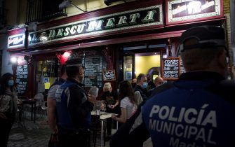 epa09186882 Local police agents control so as the bars and restaurants close at the time set due to the curfew as hundreds of people celebrate in nearby Madrid's Puerta del Sol the end of the alarm state, late on 08 May 2021.  EPA/Luca Piergiovanni