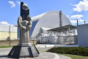 """A general view shows the monument in """"memory of the victims of the Chernobyl nuclear disaster"""" in front of Chernobyl's New 108 metres (355 feet) Safe Confinement covering the 4th block (reactor 4) of Chernobyl Nuclear power plant on April 23, 2018. - Ukraine on April 26, 2018 will mark the 32nd anniversary of the Chernobyl disaster which was the world's worst nuclear accident. (Photo by Sergei SUPINSKY / AFP)        (Photo credit should read SERGEI SUPINSKY/AFP via Getty Images)"""