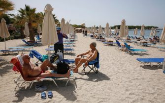 epa09186817 People enjoy a sunny day at the beach at a resort near Athens, Greece, 08 May 2021 (issued 09 May 2021). Equipped beaches charging entrance fees reopened on 08 May based on safety protocols.  EPA/ALEXANDROS VLACHOS