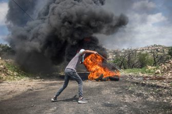 Palestinian is seen using a slingshot against Israeli soldiers during the clashes Palestinians clashed with the Israeli army during a demonstration in the village of Kafr Qaddum on May 10, 2019. Palestinians march every Fridays and Saturdays in the village of Kafr Qaddum since 2011 due to the closure of one of their roads and land confiscation by the Israeli authorities. These decisions were made to expand the Israeli settlement of Kedumim. Through this road, Palestinians were able to reach the main city of Nablus in 15 minutes, now it takes more than 45 minutes.