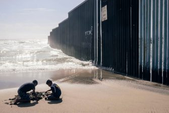 Two children play in the sand next to the wall that separates Mexico from the United States. The border in Tijuana began to be demarcated with a fence in 1990, with George Bush Sr. From 1993, Bill Clinton had an impassable fence of 14 kilometers built there. 08/05/2017 Tijuana, Baja California, Mexico.