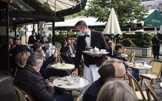 Parisians enjoy a coffee on a terrace in the morning on May 19, 2021 in Paris. Bars, shops and cultural spaces across France reopen as the country starts lifting restrictions aimed at preventing the spread of coronavirus. As of Wednesday, groups of up to six people will be allowed to eat together at outdoor restaurant terraces. France's nationwide curfew is also being pushed back from 19:00 to 21:00. Photo by Eliot Blondet/ABACAPRESS.COM