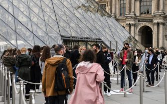 People queue outside the Louvre Museum in Paris on May 19, 2021, as museums reopen in France today as part of an easing of the nationwide lockdown due to the Covid-19 pandemic with Cafes and restaurants terraces reopening at 50-percent capacity for groups of up to six while the curfew will be pushed back from 7 to 9:00 pm. - A second phase of a lockdown-lifting plan should culminate in a full reopening of the economy on June 30. Cinemas and theatres are also reopening after being closed for more than six months, during which they relied chiefly on state aid to remain afloat. (Photo by Alain JOCARD / AFP) (Photo by ALAIN JOCARD/AFP via Getty Images)