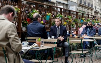 TOPSHOT - French President Emmanuel Macron (R) and French Prime Minister Jean Castex (L) are having coffees at a cafe terrace in Paris on May 19, 2021, as restaurant and bar terraces reopen today at 50-percent capacity for groups of up to six while the curfew will be pushed back from 7 to 9:00 pm, as part of an easing of the nationwide lockdown due to the Covid-19 pandemic. - Cafes and restaurants with terraces or rooftop gardens have been inundated with bookings for the return of outdoor dining, under the second phase of a lockdown-lifting plan that should culminate in a full reopening of the economy on June 30. Museums, cinemas and theatres are also reopening after being closed for more than six months, during which they relied chiefly on state aid to remain afloat. (Photo by GEOFFROY VAN DER HASSELT / AFP) (Photo by GEOFFROY VAN DER HASSELT/AFP via Getty Images)