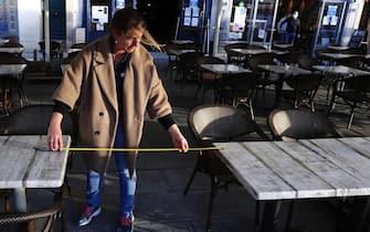 Il personale di un bar di Montpellier posiziona i tavoli alla giusta distanza