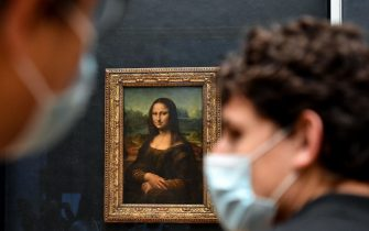 """TOPSHOT - Visitors walk past the painting """"La Joconde"""" The Mona Lisa by Italian artist Leonardo Da Vinci on display in a gallery at The Louvre Museum in Paris on May 19, 2021, as museums re-open in France as part of an easing of the nationwide lockdown due to the Covid-19 pandemic with Cafes and restaurants terraces reopening at 50-percent capacity for groups of up to six while the curfew will be pushed back from 7 to 9:00 pm. - A second phase of a lockdown-lifting plan should culminate in a full reopening of the economy on June 30. Cinemas and theatres are also reopening after being closed for more than six months, during which they relied chiefly on state aid to remain afloat. (Photo by ALAIN JOCARD / AFP) (Photo by ALAIN JOCARD/AFP via Getty Images)"""