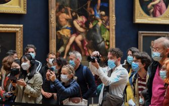 """Visitors gather behind a barrier as they look at the painting """"La Joconde"""" The Mona Lisa by Italian artist Leonardo Da Vinci on display in a gallery at The Louvre Museum in Paris on May 19, 2021, as museums re-open in France as part of an easing of the nationwide lockdown due to the Covid-19 pandemic with Cafes and restaurants terraces reopening at 50-percent capacity for groups of up to six while the curfew will be pushed back from 7 to 9:00 pm. - A second phase of a lockdown-lifting plan should culminate in a full reopening of the economy on June 30. Cinemas and theatres are also reopening after being closed for more than six months, during which they relied chiefly on state aid to remain afloat. (Photo by ALAIN JOCARD / AFP) (Photo by ALAIN JOCARD/AFP via Getty Images)"""