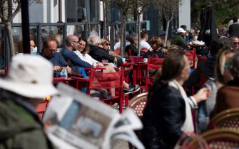 People sit a cafe terraces in Le Palais, in the Britanny island of Belle-Ile-en-Mer, on May 19, 2021, as restaurant and bar terraces reopen today at 50-percent capacity for groups of up to six while the curfew will be pushed back from 7 to 9:00 pm, as part of an easing of the nationwide lockdown due to the Covid-19 pandemic. - Cafes and restaurants with terraces or rooftop gardens have been inundated with bookings for the return of outdoor dining, under the second phase of a lockdown-lifting plan that should culminate in a full reopening of the economy on June 30. Museums, cinemas and theatres are also reopening after being closed for more than six months, during which they relied chiefly on state aid to remain afloat. (Photo by LOIC VENANCE / AFP) (Photo by LOIC VENANCE/AFP via Getty Images)