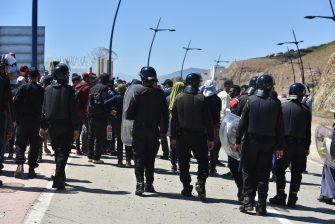 epa09212283 Moroccan anti-riot police stand guard to prevent the passage of people trying to reach the Ceuta-Tarajal border crossing at the road between Fnidq close to the Spanish city of Ceuta, located in northern Africa, 19 May 2021. Around 8,000 migrants, many from Sub-Saharan Africa and including 1,500 minors, entered the enclave on 18 and 19 May by swimming in or climbing over the fence between the Spanish-Moroccan border. Morocco has locked down the Ceuta-Tarajal border crossing as of 19 May.  EPA/JALAL MORCHIDI
