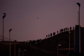 epaselect epa09210460 Migrants tries to cross the border of Tarajal in Ceuta, Spain, 18 May 2021. In little over 24 hours a total of almost 8,000 people entered into the Spanish city of Ceuta, located in the North African coast, by sea side and hundreds of migrants continue to attempt doing so. The Spanish authorities have deployed the army to patrol on the border separating Ceuta in the Spanish side from the Moroccan side, in a bid to control this latest surge of entry attempts.  EPA/BRAIS LORENZO