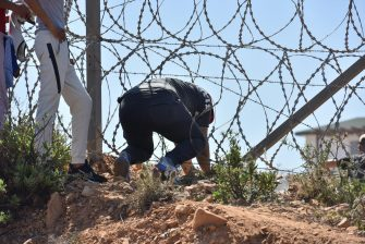 epa09210802 Migrants sneak under the fence in the northern town of Fnideq in an attempt to cross the border from Morocco to the Spanish enclave of Ceuta, in North Africa 18 May 2021.  In little over 24 hours a total of almost 8,000 people entered into the Spanish city of Ceuta, located in the North African coast, by sea side and hundreds of migrants continue to attempt doing so. The Spanish authorities have deployed the army to patrol on the border separating Ceuta in the Spanish side from the Moroccan side, in a bid to control this latest surge of entry attempts.  EPA/JALAL MORCHIDI
