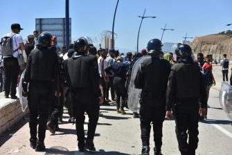epa09212288 Moroccan anti-riot police stand guard to prevent the passage of people trying to reach the Ceuta-Tarajal border crossing at the road between Fnidq close to the Spanish city of Ceuta, located in northern Africa, 19 May 2021. Around 8,000 migrants, many from Sub-Saharan Africa and including 1,500 minors, entered the enclave on 18 and 19 May by swimming in or climbing over the fence between the Spanish-Moroccan border. Morocco has locked down the Ceuta-Tarajal border crossing as of 19 May.  EPA/JALAL MORCHIDI
