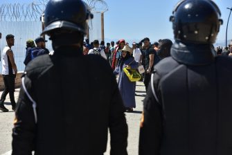 epa09212284 Moroccan anti-riot police stand guard to prevent the passage of people trying to reach the Ceuta-Tarajal border crossing at the road between Fnidq close to the Spanish city of Ceuta, located in northern Africa, 19 May 2021. Around 8,000 migrants, many from Sub-Saharan Africa and including 1,500 minors, entered the enclave on 18 and 19 May by swimming in or climbing over the fence between the Spanish-Moroccan border. Morocco has locked down the Ceuta-Tarajal border crossing as of 19 May.  EPA/JALAL MORCHIDI