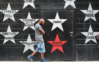 epa09224582 A person looks at the George Floyd star on the wall of the First Avenue rock club as protesters march through the streets to commemorate the anniversary of George Floyd's death in Minneapolis, Minnesota, USA, 23 May 2021. The rally and march is part of several days of events to mark the one year anniversary of FloydÕs death that sparked the Black Lives Matter movement around the world.  EPA/CRAIG LASSIG